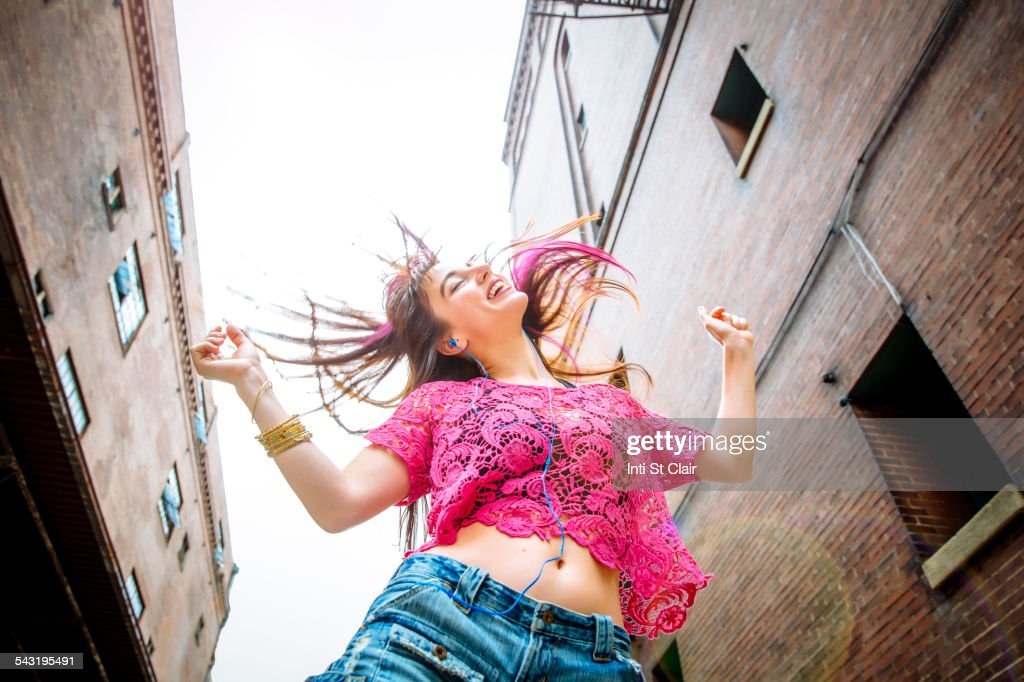 Low angle view of Caucasian woman dancing outdoors : Stock Photo