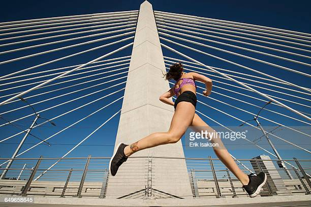 Low angle view of Caucasian woman jogging on urban bridge