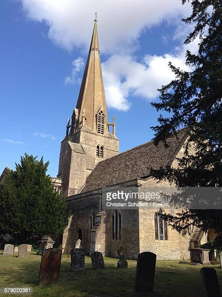 low angle view of cemetery by church against sky - bampton stock pictures, royalty-free photos & images