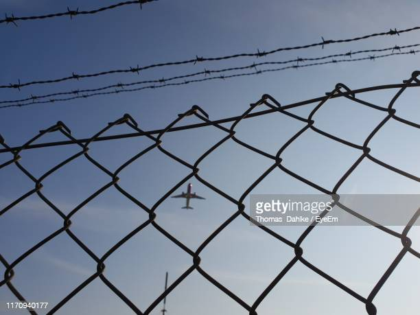 low angle view of chainlink fence against airplane - low flying aircraft stock pictures, royalty-free photos & images