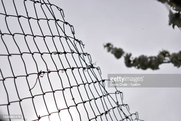 low angle view of chainlink fence against sky - chainlink fence stock pictures, royalty-free photos & images