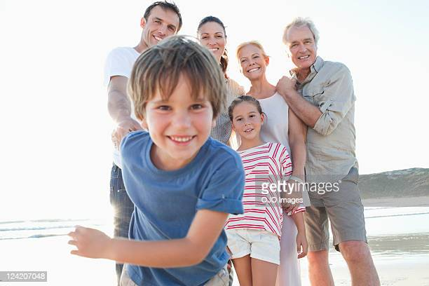 Low angle view of cheerful boy enjoying on a beach with family