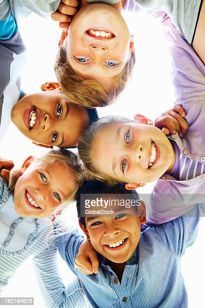 low angle view of cheerful children huddling together - vertical stock pictures, royalty-free photos & images