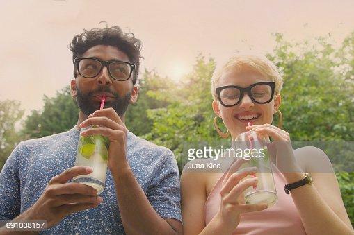 Low angle view of cheerful couple drinking lemonade at yard