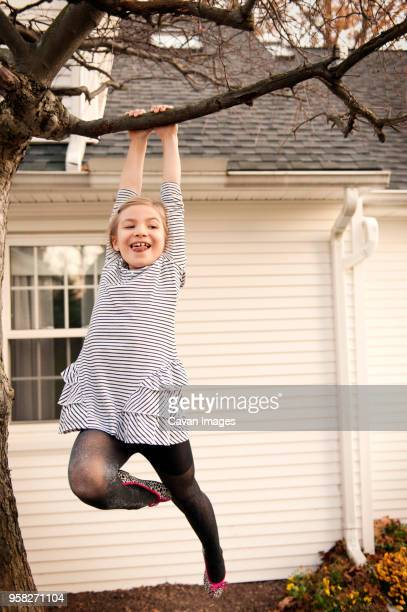 low angle view of cheerful girl hanging from tree in yard - hanging stock pictures, royalty-free photos & images