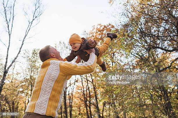 Low angle view of cheerful man lifting baby boy at park during autumn