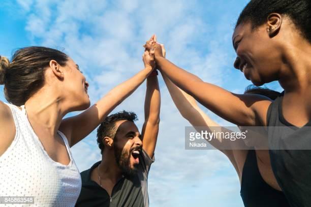 vista de ângulo baixo de alegres amigos desportivos com os braços levantados - quatro pessoas - fotografias e filmes do acervo