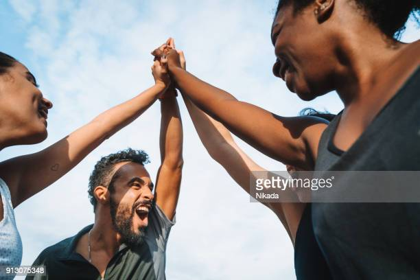 Low angle view of cheerful sporty friends with arms raised