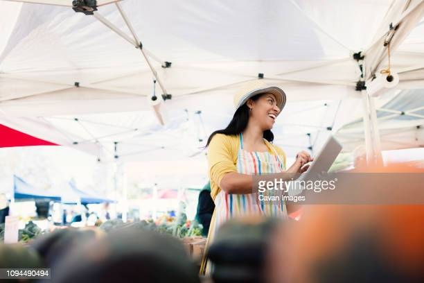 Low angle view of cheerful vendor holding tablet computer while looking away at farmer's market