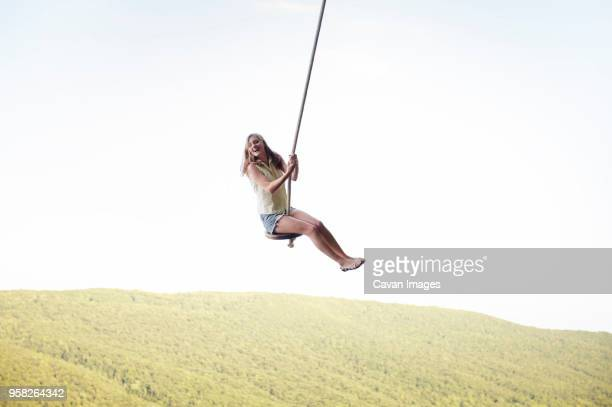 Low angle view of cheerful woman swinging on rope against clear sky