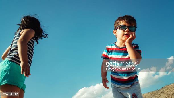 Low Angle View Of Child Against Blue Sky