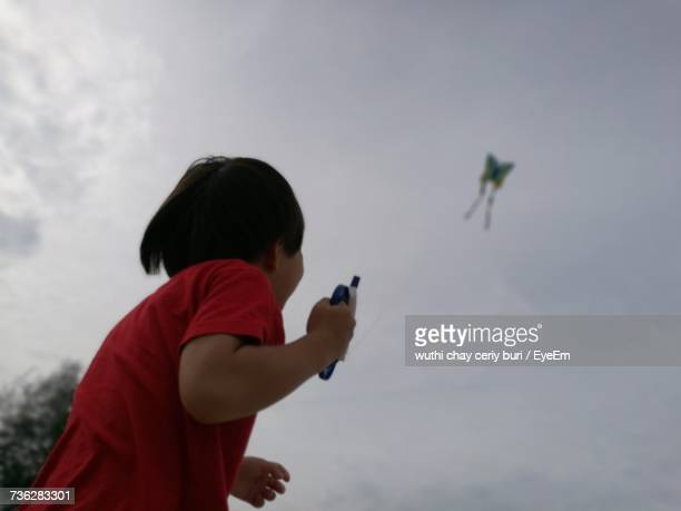 Low Angle View Of Child Flying Kite Against Cloudy Sky