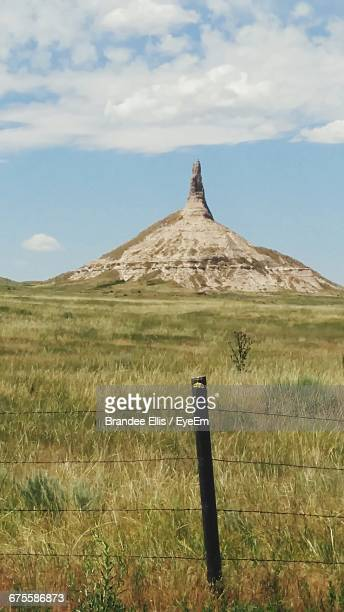 Low Angle View Of Chimney Rock In Front Of Grassy Field Against Sky On Sunny Day