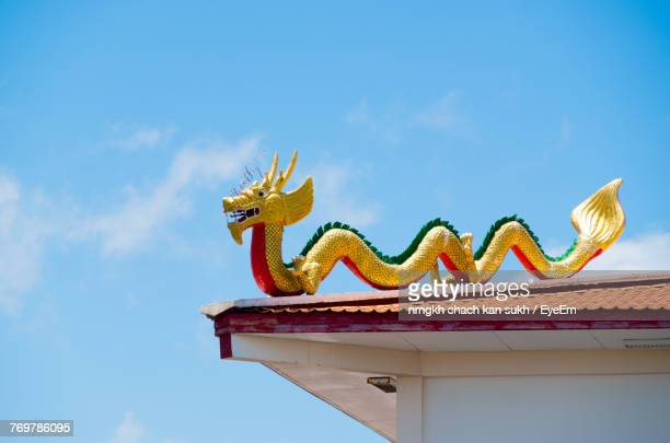 low angle view of chinese dragon against blue sky - chinese dragon stock photos and pictures