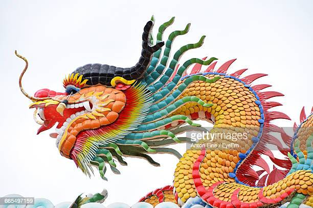 low angle view of chinese dragon at temple against clear sky - chinese dragon stock photos and pictures