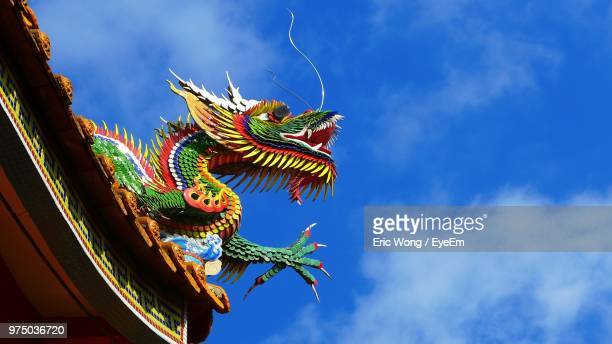 low angle view of chinese dragon on roof against blue sky - chinese dragon stock pictures, royalty-free photos & images