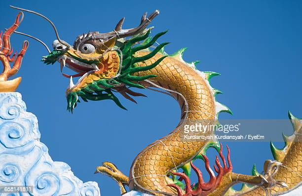 low angle view of chinese dragon statue against clear sky - chinese dragon stock photos and pictures
