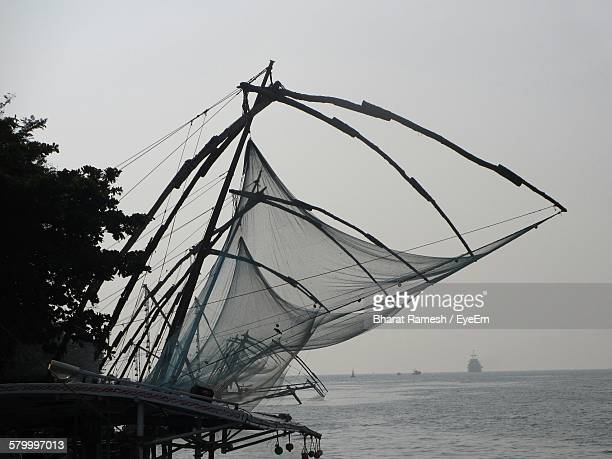 Low Angle View Of Chinese Fishing Nets By Sea Against Clear Sky