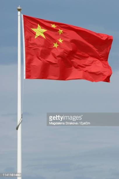 low angle view of chinese flag against sky - flagpole stock pictures, royalty-free photos & images