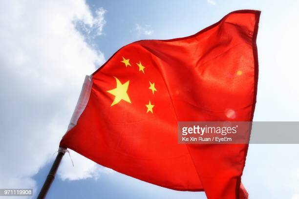 low angle view of chinese flag waving against sky - chinese flag stock pictures, royalty-free photos & images