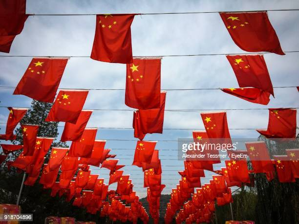 low angle view of chinese flags hanging against sky - chinese flag stock pictures, royalty-free photos & images