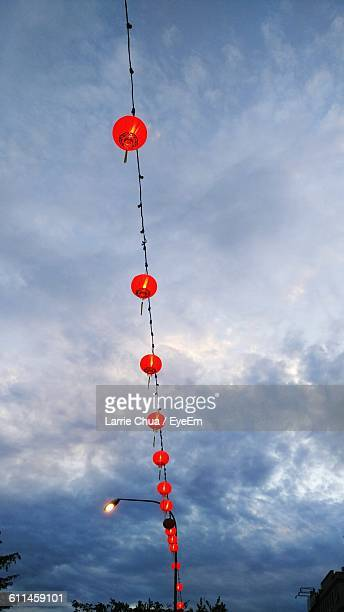 Low Angle View Of Chinese Lanterns Hanging Against Cloudy Sky At Dusk
