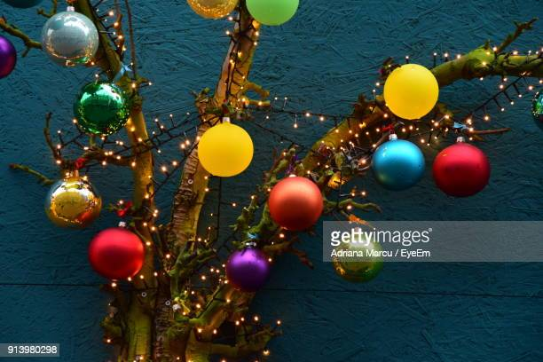 Low Angle View Of Christmas Decorations Hanging On Tree Against Wall