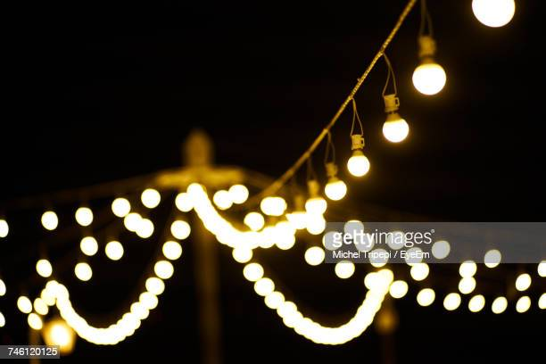 Low Angle View Of Christmas Light Strings Against Sky During Night