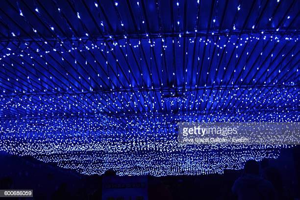 Low Angle View Of Christmas Lights On Ceiling Of Covered Walkway