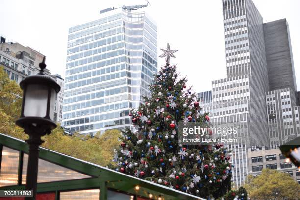 low angle view of christmas tree against office buildings at bryant park - new york city christmas stock photos and pictures