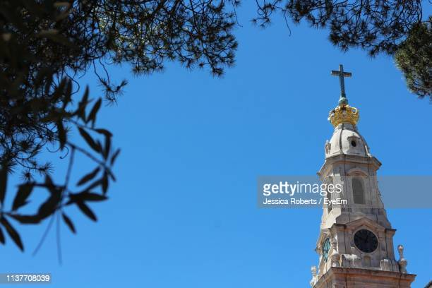 low angle view of church against blue sky - fatima portugal photos et images de collection