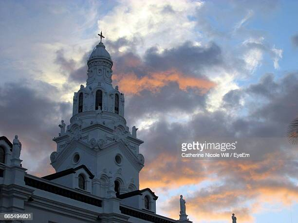 Low Angle View Of Church Against Cloudy Sky At Dusk