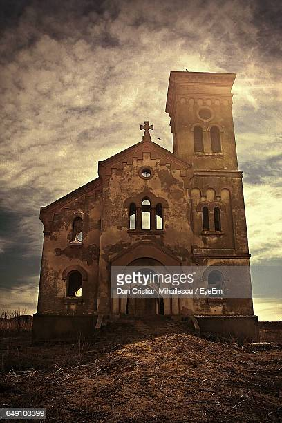 Low Angle View Of Church Against Cloudy Sky During Sunny Day