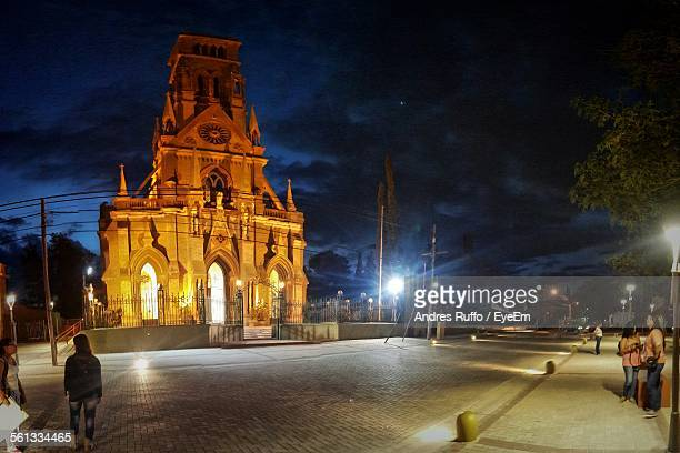 low angle view of church by illuminated street against cloudy sky at night - andres ruffo stock photos and pictures