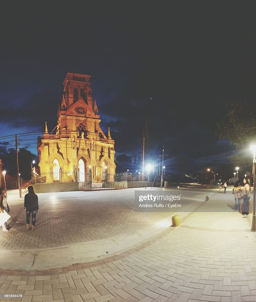 Low Angle View Of Church By Illuminated Street Against Cloudy Sky At Night : Stock-Foto