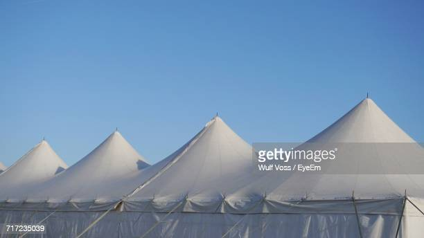 low angle view of circus tent against clear blue sky - entertainment tent stock pictures, royalty-free photos & images