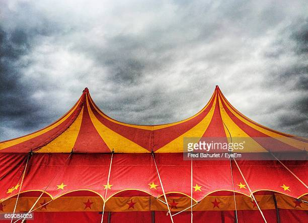 low angle view of circus tent against cloudy sky - circus stock pictures, royalty-free photos & images