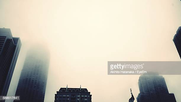 Low Angle View Of City Buildings Against Sky During Foggy Weather