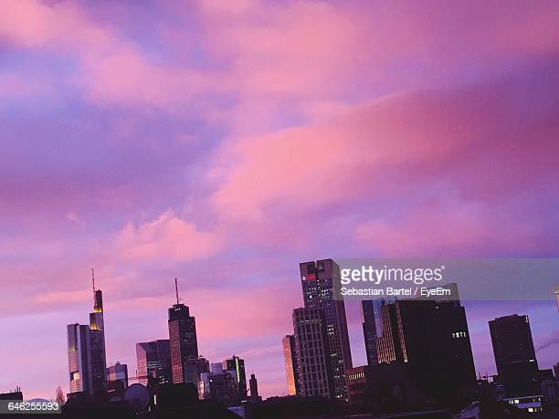 Low Angle View Of Cityscape Against Cloudy Sky During Sunset