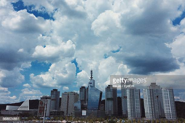 low angle view of cityscape against cloudy sky - daejeon stockfoto's en -beelden