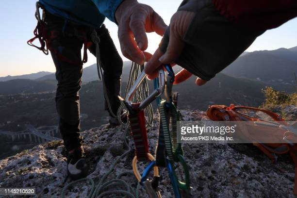 Low angle view of climbers exchanging gear on rock summit at sunset