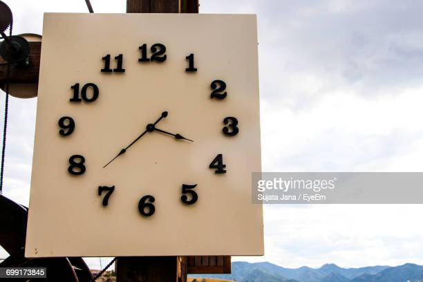 Low Angle View Of Clock Against Cloudy Sky