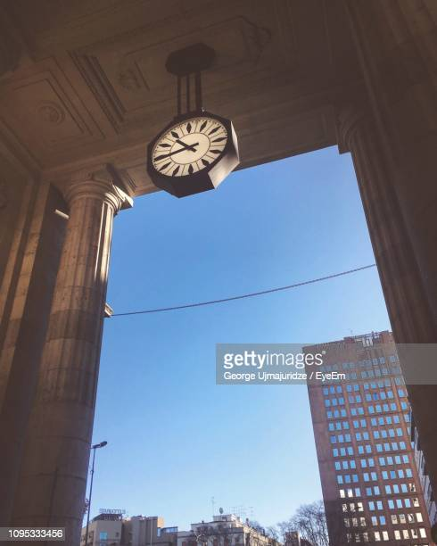 Low Angle View Of Clock Hanging From Ceiling Against Clear Blue Sky