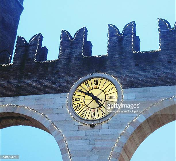 Low Angle View Of Clock On Wall Against Sky At Dusk
