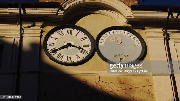 low angle view of clock on wall - gianluca langella imagens e fotografias de stock