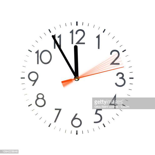 low angle view of clock on white background - wall clock stock photos and pictures