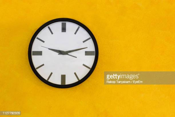 low angle view of clock on yellow wall - wall clock stock photos and pictures