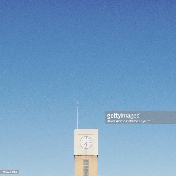 low angle view of clock tower against blue sky - javier alonso fotografías e imágenes de stock