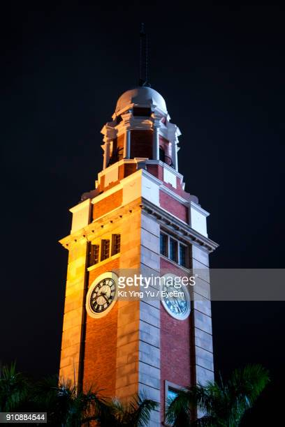 low angle view of clock tower against clear sky at night - 時計台 ストックフォトと画像