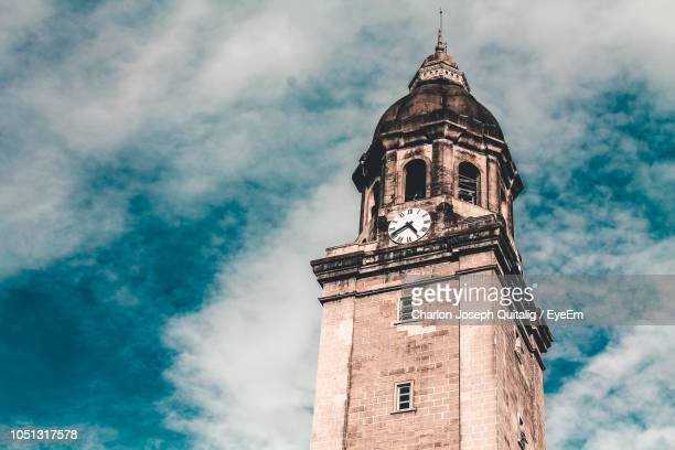 low angle view of clock tower against cloudy sky - old manila stock pictures, royalty-free photos & images